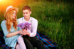 Young couple sitting on the plaid in the park and look at the sunset, man gives his girlfriend a bouquet of lilacs Royalty Free Stock Image