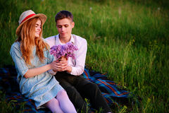 Young couple sitting on the plaid in the park and look at the sunset, man gives his girlfriend a bouquet of lilacs Stock Photo