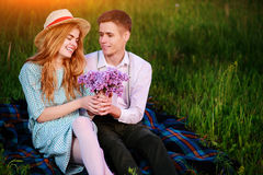 Young couple sitting on the plaid in the park and look at the sunset, man gives his girlfriend a bouquet of lilacs Royalty Free Stock Photos