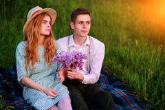 Young couple sitting on the plaid in the park and look at the sunset, man gives his girlfriend a bouquet of lilacs Stock Images