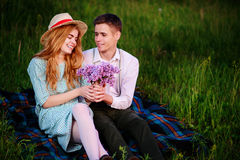 Young couple sitting on the plaid in the park and look at the sunset, man gives his girlfriend a bouquet of lilacs Stock Image