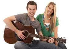 Young couple sitting playing guitar looking at camera Royalty Free Stock Image