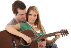 Young couple sitting playing guitar peaceful faces Stock Photo