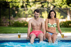 Young couple sitting at poolside Stock Photos