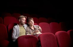 Young couple sitting at red movie theatre stock images