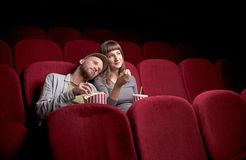 Young couple sitting at red movie theatre royalty free stock photo