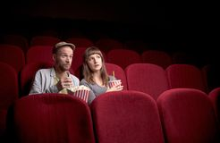 Young couple sitting at red movie theatre royalty free stock images