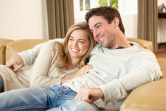 Young couple sitting and relaxing on sofa Stock Photos