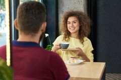 Young couple sitting in restaurant, drinking coffee, smiling, talking. Girl holding blue cup, looking at camera, having curly hair, wearing yellow blouse. Back Royalty Free Stock Image