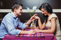 Young couple sitting in restaurant and flirting. Young couple sitting in restaurant, flirting and drinking wine Royalty Free Stock Images