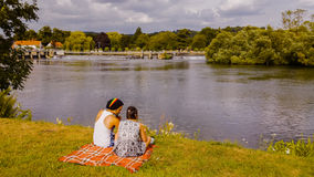 Young Couple Sitting on River Bank. A young couple sitting and talking on the bank of the River Thames near Hambleden lock on a sunny day. Buckinghamshire Stock Photos