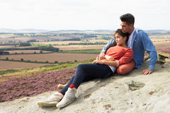 Young Couple Sitting On Rock Admiring View Royalty Free Stock Photos