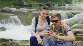 A young couple is sitting on a rock against a background of a rugged mountain river. They use a smartphone. Technology. And travel concept. 4K video stock video footage