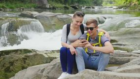 A young couple is sitting on a rock against a background of a rugged mountain river. They use a smartphone. Technology. And travel concept. 4K video stock video