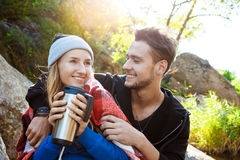 Young couple sitting on rock in canyon, smiling, drinking tea. Stock Photos