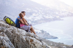 Young couple sitting on rock and enjoying beautiful view. Royalty Free Stock Photos