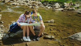 A young couple is sitting on a rock near a mountain river. They look at the map together. Planning the route and