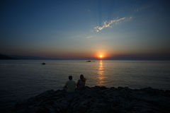 Young couple sitting on a rock near the sea and watching the sun. Young lovely couple sitting on a rock near the sea and watching the sun Royalty Free Stock Photography