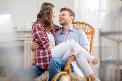 Young couple sitting in rocking chair and looking at each other Royalty Free Stock Photo