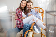 Young couple sitting in rocking chair and smiling at camera Stock Images