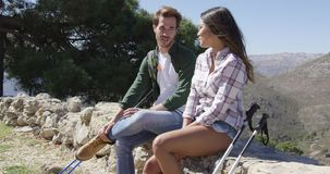 Young couple sitting on rocks in mountains. Young romantic couple sitting on rock fence and having rest while hiking high in mountains stock footage