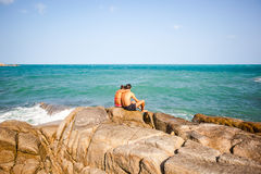 Young couple sitting on the rocks near shore and Stock Photo