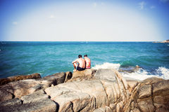 Young couple sitting on the rocks near shore and Stock Image