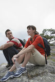 Young Couple Sitting On Rocks By Ocean Stock Image
