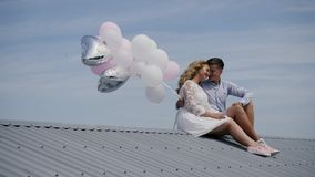 Young couple sitting on the roof with balloons on the blue sky background stock photos