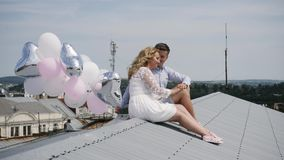 Young couple sitting on the roof with balloons. stock images