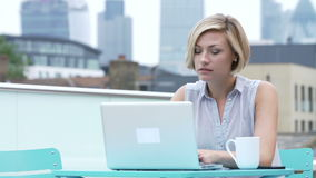 Young Couple Sitting On Roof Terrace Using Laptop. Young woman sitting on roof terrace with urban skyline in background, using laptop is greeted by male friend stock footage