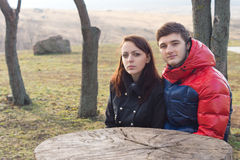 Young couple sitting at a rustic picnic table Royalty Free Stock Photo