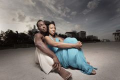 Young couple sitting on the sand Stock Photos