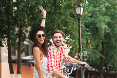 Young couple sitting on scooter and smiling. Back view of happy young couple wearing stylish clothes sitting on scooter, posing and smiling on a summer day Stock Images