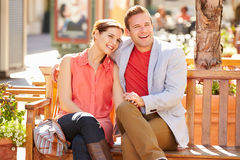 Young Couple Sitting On Seat In Mall Together Stock Photos