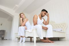 Young Couple Sitting Separate On Bed, Having Conflict Relationships Problem, Sad Negative Emotions Hispanic Man And. Woman Lovers Argue In Bedroom Stock Photography