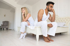 Young Couple Sitting Separate On Bed, Having Conflict Relationships Problem, Sad Negative Emotions Hispanic Man And Stock Image