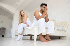 Young Couple Sitting Separate On Bed, Having Conflict Relationships Problem, Sad Negative Emotions Hispanic Man And Royalty Free Stock Photo