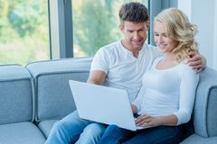 Young couple sitting sharing a laptop computer Stock Image