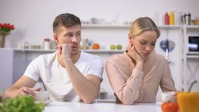 Young couple sitting silently in kitchen after argument, crisis in relationship. Stock footage stock video footage