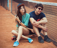 Young couple sitting on a skateboard on the tennis court Stock Photography