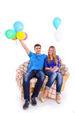 Young couple sitting on a sofa with balloons Royalty Free Stock Photo