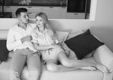 Young couple sitting at sofa Stock Photography