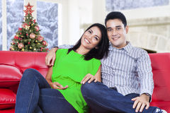 Young couple sitting on sofa with christmas tree Royalty Free Stock Photography