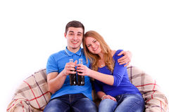 Young couple sitting on a sofa and drinking soda i Stock Photography