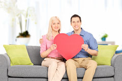 Young couple sitting at sofa and holding big red heart. Indoors Stock Photos