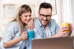 Young couple looking at laptop at home. Young couple sitting on sofa at home, drinking coffee and looking at laptop, enjoying free time Stock Images