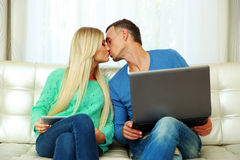 Young couple sitting at the sofa with laptop Stock Photo