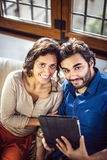 Young Couple Sitting On Sofa Using Digital Tablet Royalty Free Stock Photography