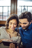 Young Couple Sitting On Sofa Using Digital Tablet Royalty Free Stock Photo